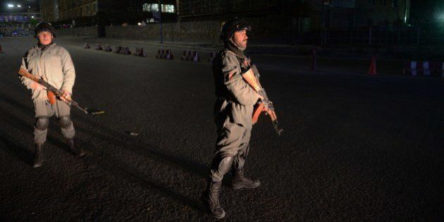 Afghan policemen block a road near the security perimeter of the Serena hotel in Kabul early on March...