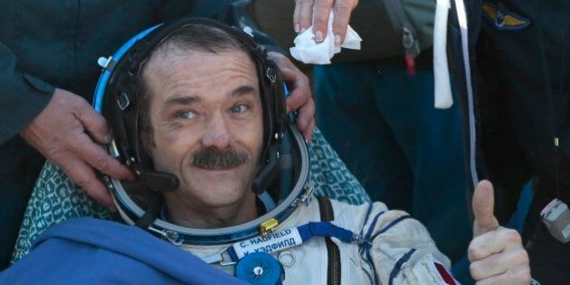 Canadian spaceman Chris Hadfield gives a thumb up shortly after the landing aboard the Russian Soyuz...