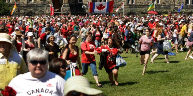 Spectators run for a position to see Prince William and Kate, the Duke and Duchess of Cambridge at a Canada Day celebration on Parliament Hill in Ottawa, Canada Friday, July 1, 2011. (AP Photo/Charlie Riedel)