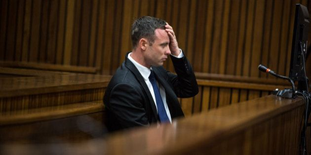 South African Paralympic athlete Oscar Pistorius takes notes in the dock on day eleven of his trial for...
