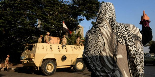 An Egyptian woman waves to soldiers on top of an armoured vehicle guarding the entrance of a military...