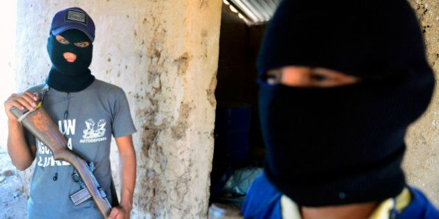 Two former 'punteros' (informants) of the Templar Knights drug cartel pose during an interview with AFP...