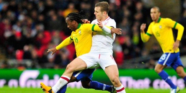 England's midfielder Jack Wilshere (R) reaches across to try to tackle Brazil's midfielder Arouca (L)...