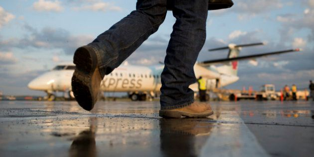 A traveller walks to an Air Canada Express aircraft at the Fort McMurray airport in Fort McMurray, Alberta,...