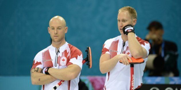 Canada's Brad Jacobs (R) talks with his teammate Ryan Fry during the 2014 Sochi winter olympics men's...