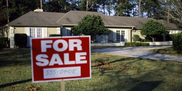 For sale sign board in the front yard of a
