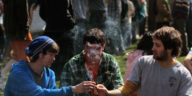 BOULDER, CO - APRIL 20: Young men smoke a marijuana cigarette during a 'smoke out' with thousands of...