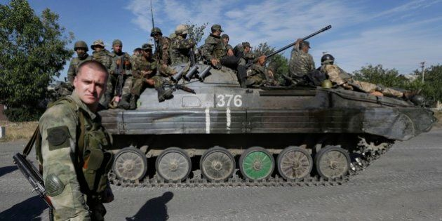 A pro-Russian rebel watches as Ukrainian troops evacuated from the rebel-held town of Starobesheve, eastern...