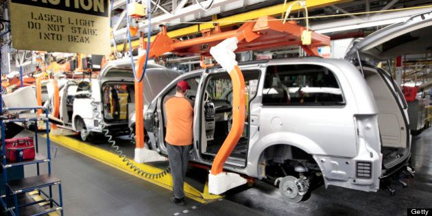 A Chrysler Group LLC employee works on a Chrysler minivan as it moves down the production line at Chrysler...