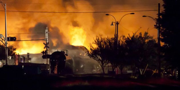 Firefighters douse blazes after a freight train loaded with oil derailed in Lac-Megantic in Canada's...