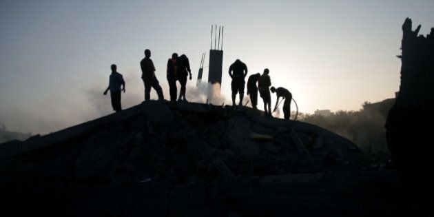 Palestinians try to salvage what they can of their belongings from the rubble of a house destroyed by...