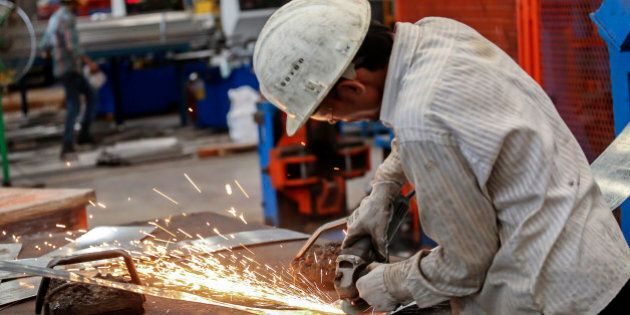 An employee uses an angle grinder on the production line of the tube mill at the manufacturing facility...