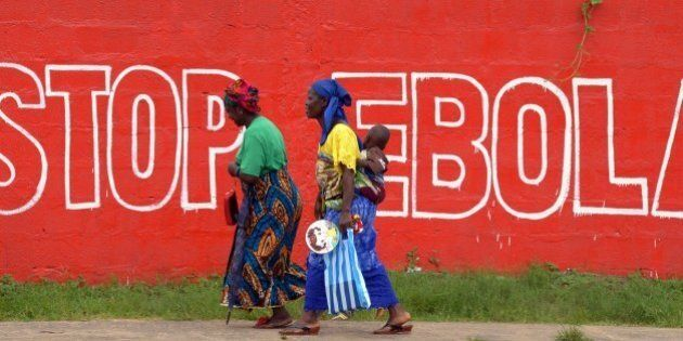 Women walk past a slogan painted on a wall reading 'Stop Ebola' in Monrovia on August 31, 2014. Liberia...