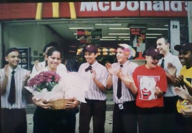 Sheilla Azevedo (à esquerda, segurando flores) no início de sua carreira no McDonald's no final dos anos 90.