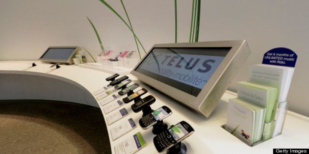 Mobile phones sit on display at a Telus Corp. learning center and store in Toronto, Ontario, Canada,...