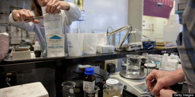 Employee Danny Crawford, left, cuts a special film to cover a flask while research and development chemist...