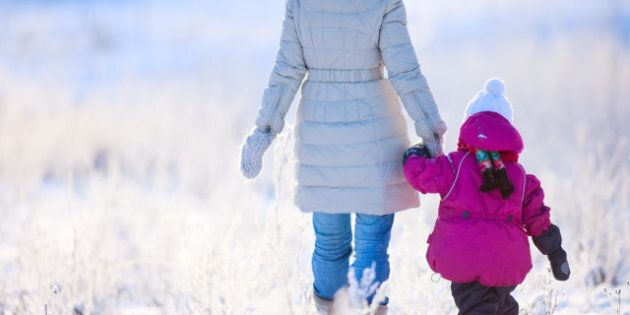 Back view of mother and daughter walking on winter day