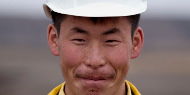 In this July 6, 2012 photo, a Mongolian miner smiles while working at Erdenes Tavan Tolgoi, a coal mining...