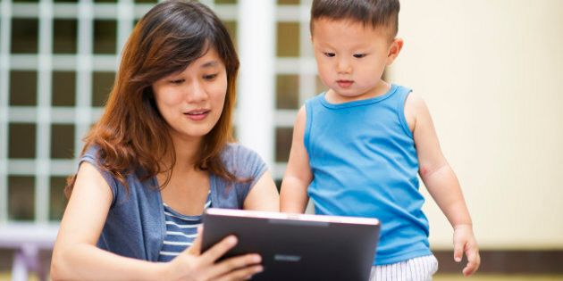 Mother and little boy looking at tablet in front of house.