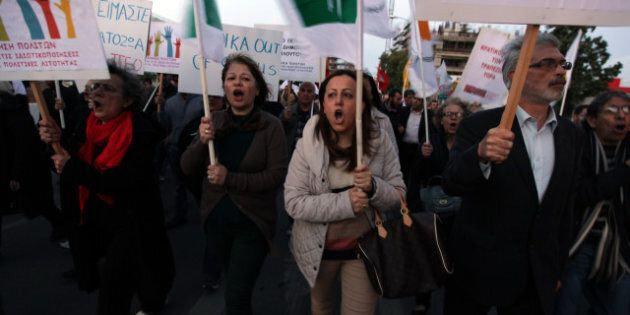 Supporters of Cyprus' communist party hold banners and shout slogans as they protest outside the presidential...