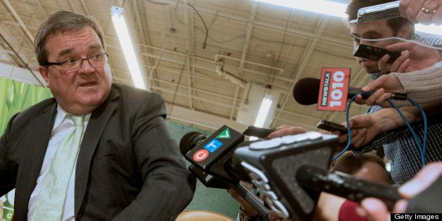 Jim Flaherty, Canada's finance minister, center, speaks to the media while trying on shoes to purchase,...