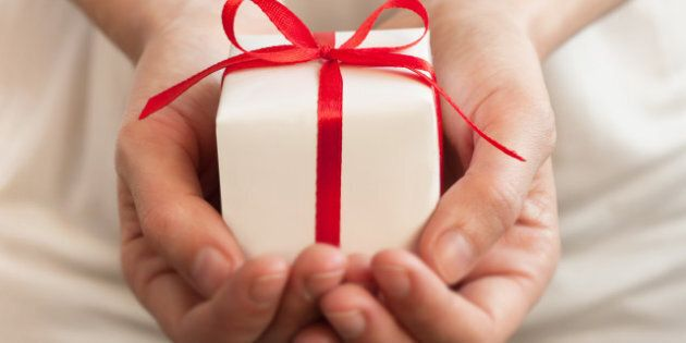 Female hands holding small gift with