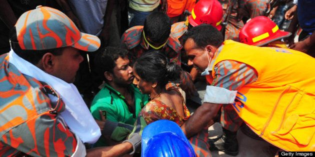 Bangladeshi firefighters rescue a garment worker (C) found alive in the collapse of an eight-storey building...
