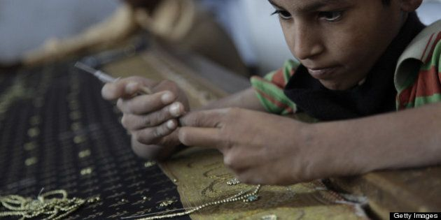 JAIPUR, INDIA - NOVEMBER 18: A young boy works in a textile factory November 18, 2009 in Jaipur, India....