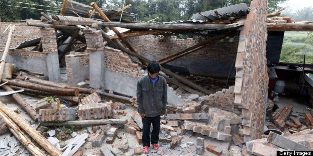 A local resident stands in ruins as he mourns in Lingguan township of Baoxing county in Yaan, southwest...