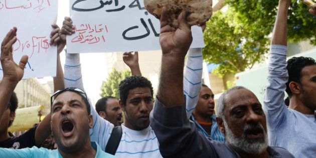 An Egyptian protester holds bread as fellow demonstrators shout slogans during a rally in downtown Cairo against the visit of a delegation from the International Monetary Fund (IMF) on April 3, 2013. An IMF delegation is in Cairo for talks on a financing programme needed to lift Egypt's economy out of crisis. The government has been walking a tight rope, as the reforms required by the international lender are likely to spark social tensions. AFP PHOTO / KHALED DESOUKI (Photo credit should read KHALED DESOUKI/AFP/Getty Images)