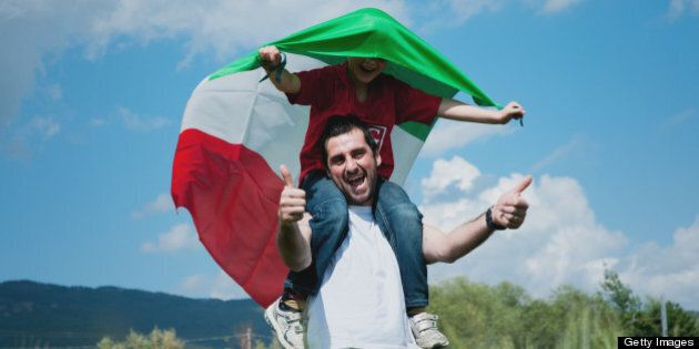 Son on dad's shoulders showing italian flag, they are walking and having fun outdoor.