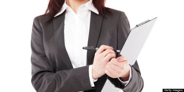 Young attractive Asian businesswoman taking writing on clipboard and looking at camera, isolated on white