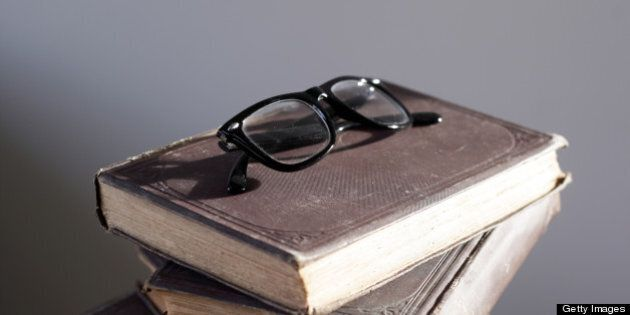 Nerdy black glasses on top of a pile of old