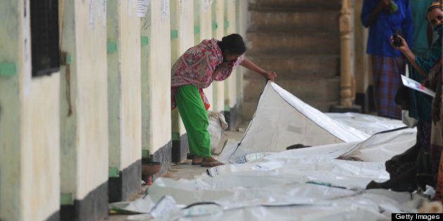 A Bangladeshi relative attempts to identify the bodies of loved ones killed in building collapse in Savar,...