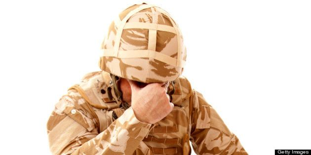 A distraught soldier on one knee with one hand covering his face, possibly suffering from shell shock...