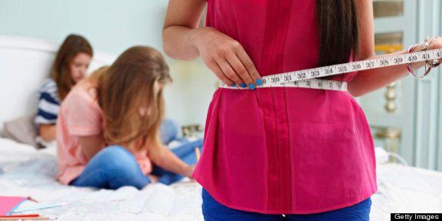 Teenage girl measuring her