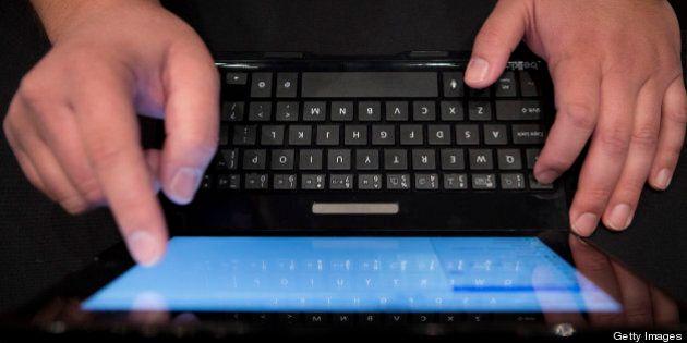 An employee types on a Belkin International Inc. 'Ultimate' tablet keyboard at Pepcom DigitalFocus in...