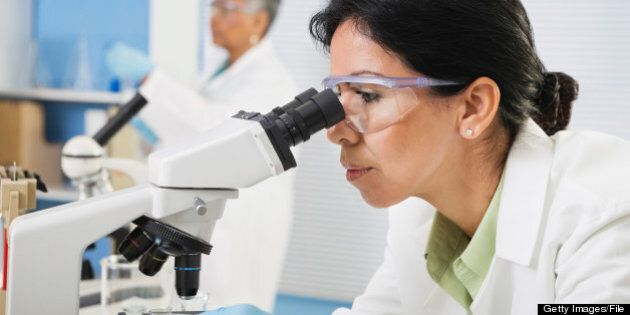 Professional female Hispanic scientist with microscope in