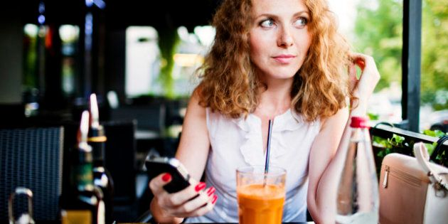 Woman with mobile phone waiting for order in a restaurant