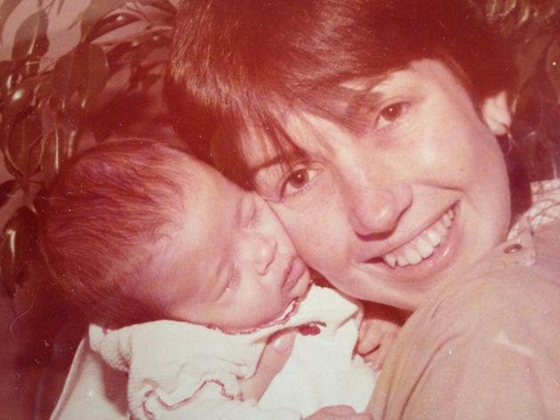 Cláudia segura sua filha, a bebê Talita, que hoje é Tatá