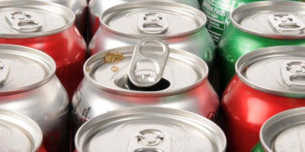 A single opened soft drink can in rows of drinks