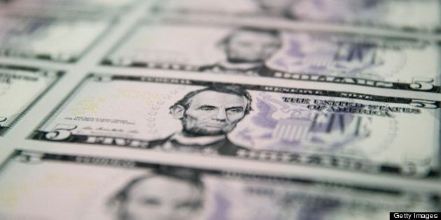 Sheets of five dollar notes sit on a pallet before being printed with a serial number at the Bureau of...