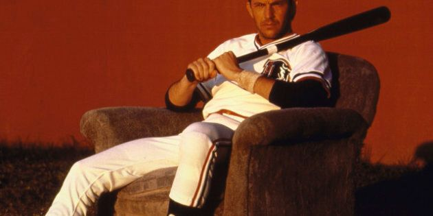 Actor Kevin Costner sitting in an upholstered chair, wearing uniform & holding a bat, during the filming...