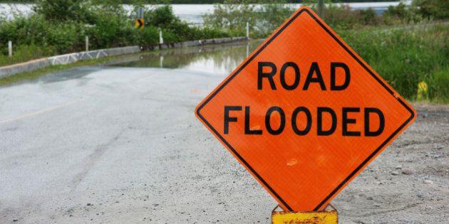 Orange caution sign saying road flooded against Fraser river flooding over