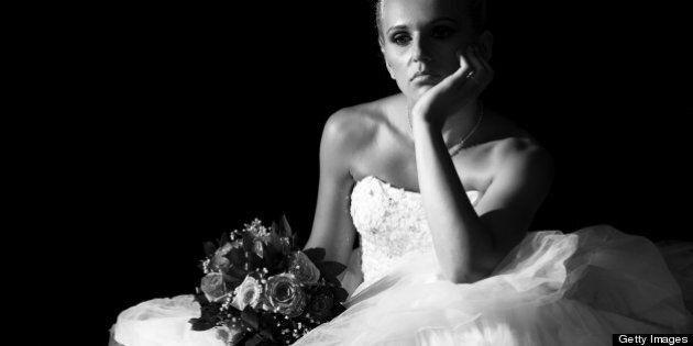 Sad bride sitting in the dark. Black and