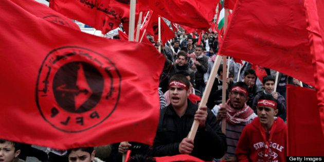 Supporters of the Popular Front for the Liberation of Palestine (PFLP) carry the party flag during a...