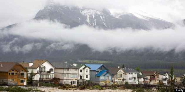CANMORE, CANADA - JUNE 21: The houses along the east side of Cougar Creek in front of Three Sisters Mountain...