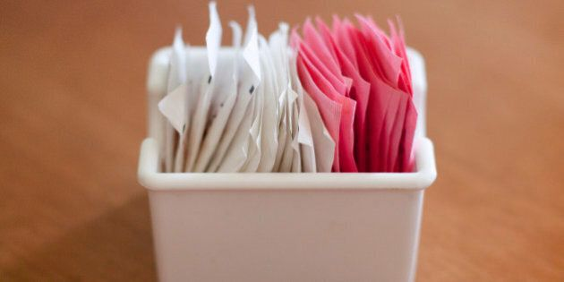 A container of sweetener and sugar packets on a
