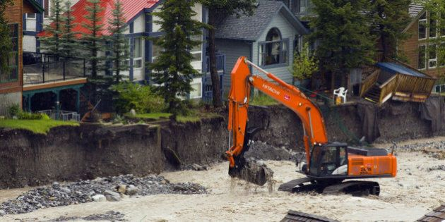 CANMORE, CANADA - JUNE 21: A man operating an excavator works to shore up the flooding Cougar Creek on...