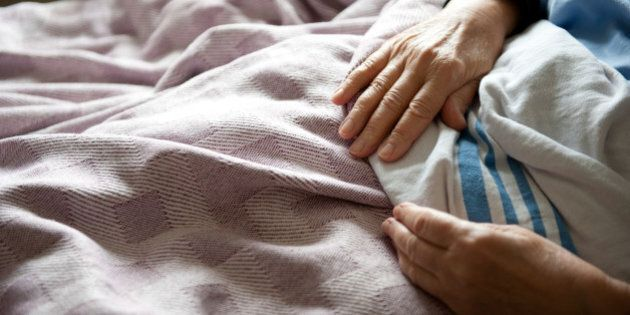 Woman's pale hands resting on sheet and blankets of her hospital